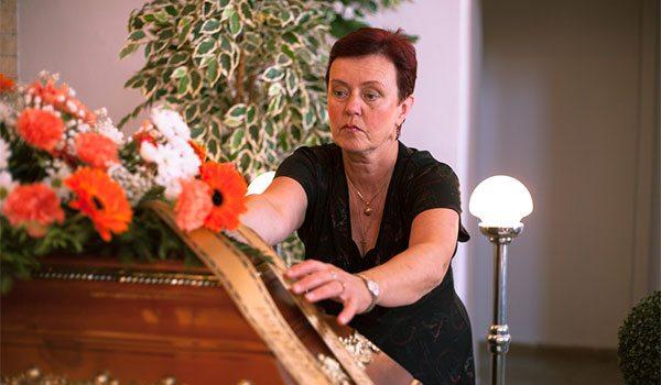 woman checks flowers on a casket