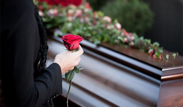 Woman holding a red rose in front of a casket with candles.