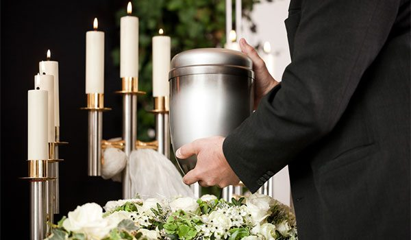 Man holding urn with cremated remains at crematorium ceremony