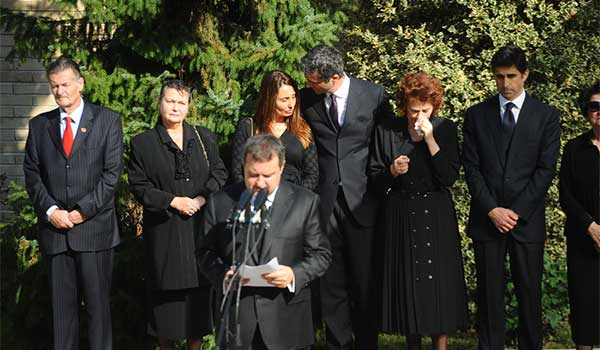 Mourners at a funeral wearing all black.
